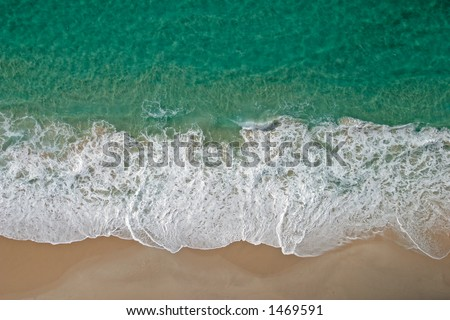 Aerial view of waves and sandy beach of the tropical coast of Mozambique - stock photo
