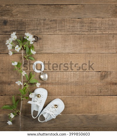 Aerial View of White Vintage Baby Shoes with Antique Teething Ring and White Flowers on Horizontal Rustic Wood Board Background with room or space for copy, text, your words, Vertical Warm toned