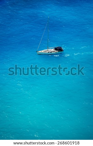 Aerial view of white yacht in deep blue sea - stock photo