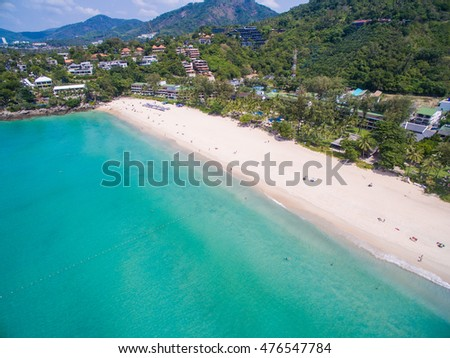 Aerial view of wide white sandy beach on tropical idyllic island with clear blue water. Almost empty. Thailand, Phuket, Kata Noi Beach.