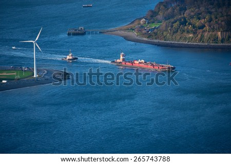 AERIAL VIEW of Wind Turbine and Tug Boat pushing red barge, Boston Harbor, MA  - stock photo