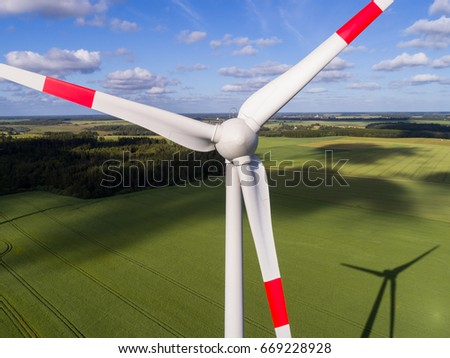 Aerial view of wind turbines on green grain field.