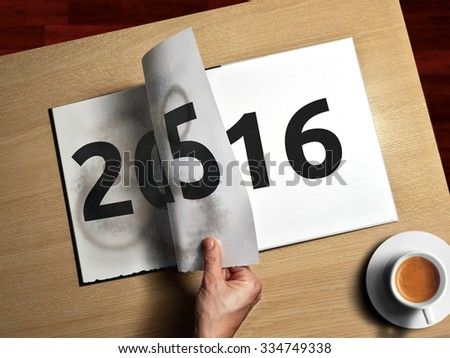 aerial view of woman hand that turn page on agenda for new year - stock photo