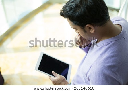 Aerial view of young man in purple sweater perusing gray silver touch-pad tablet device, fascinated, riveted, and captivated, isolated indoors background - stock photo