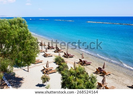 Aerial view on a beach chairs and umbrellas on sand beach. Limassol, Cyprus. Turquoise sea water. Concept for rest, relaxation, holidays, spa, resort. - stock photo