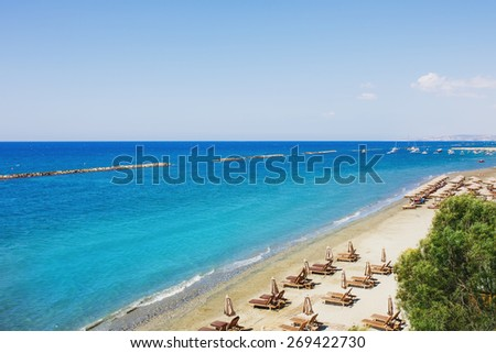 Aerial view on a beach chairs and umbrellas on sand beach. Turquoise sea water. Concept for rest, relaxation, holidays, spa, resort. Limassol, Cyprus. - stock photo