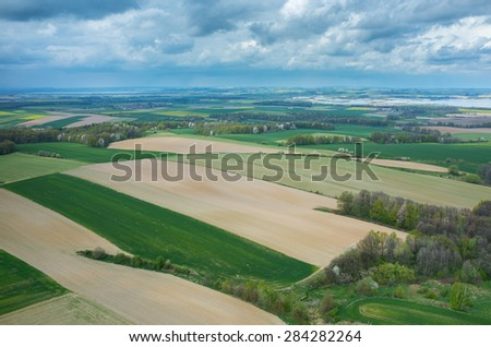 Aerial view on a small village surrounded by green fields - stock photo