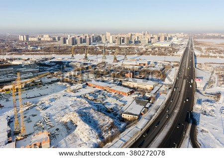 Aerial view on construction site of residential house, Tyumen river port, vehicle bridge and European residential district - stock photo