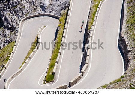 Aerial view on famous road in mountains Alps Passo Stelvio. Bikers climbing on the road