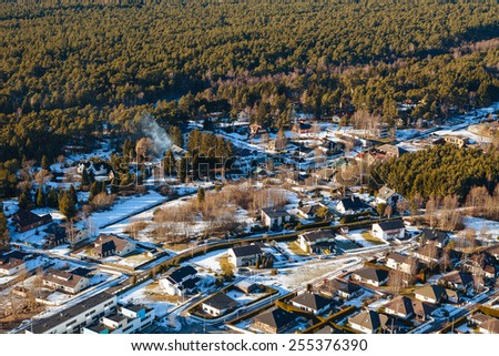 Aerial view on private houses in the forest - stock photo