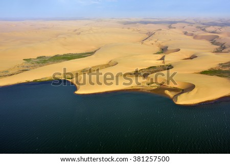 Aerial view on the coast in Namibia where dunes of the Namib desert meet with Atlantic ocean, Africa - stock photo