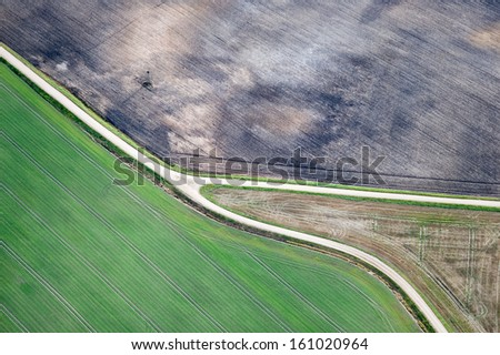 Aerial view over agricultural fields and road - stock photo