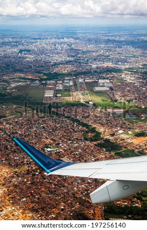 aerial view over big city with airplane wing - stock photo