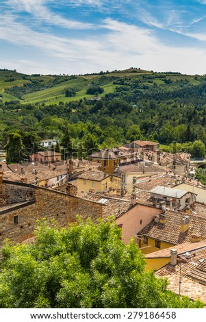 aerial view over red roofs and old houses facing each other in the old town of a country town in Italian countryside - stock photo