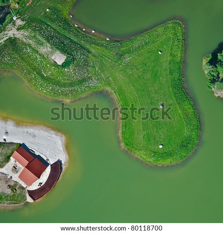 Aerial view over small lake and cottage - stock photo