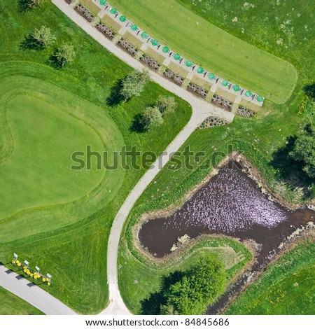 Aerial view over small lake and golf field - stock photo