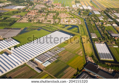 Aerial view over the Amsterdam suburbs with canals, houses , fields and greenhouses. Holland - stock photo