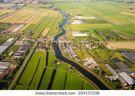 Aerial view over the Amsterdam suburbs with canals, houses , fields and industrial buildings. Holland