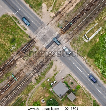 aerial view over the road intersection at the railway - stock photo