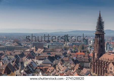Aerial view over the western part of Freiburg, a famous medieval city at the edge of the Black Forest, Germany, with its gothic cathedral in the foreground - stock photo