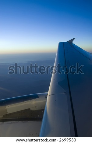 aerial view over the wing of a passenger airplane with blue sky of background