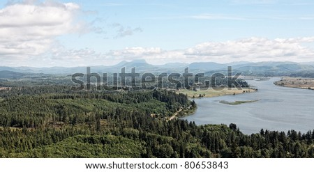 Aerial view overlooking the western coast landscape of Oregon near Astoria. Looking out over the coastal range mountains in the distance. Forested woodlands meet community inhabited land development. - stock photo