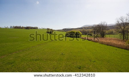 Aerial View. Panorama over a green grassy in mountains. - stock photo