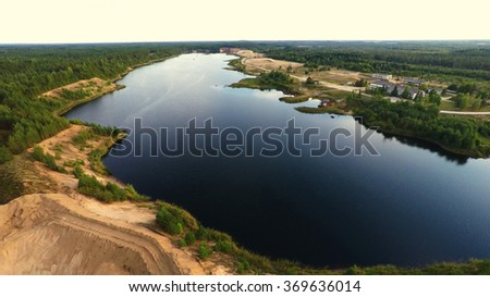 Aerial view. Quarry and lake. Nature landscape after mining. Sunset. Green forest.