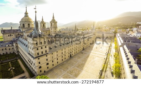 Aerial view Royal Monastery of San Lorenzo de El Escorial near Madrid, Spain against sun with strong sunbeam flare light