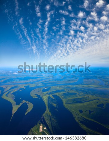 Aerial view the flood-land of great river during summer day under  white clouds. - stock photo