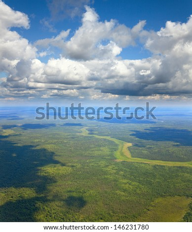 Aerial view the forest plain under white clouds in summer. - stock photo