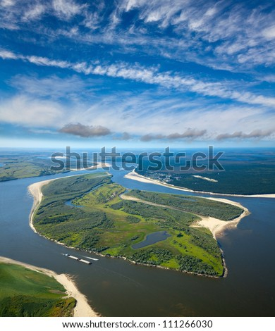 Aerial view the great river during summer day under white clouds. The ship with barge moves along the river.