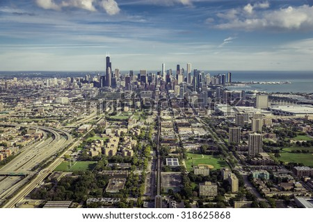 Aerial view through Chicago Downtown with suburbs - high angle - stock photo