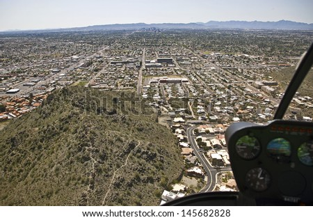 Aerial view through the bubble of a helicopter at the Phoenix, Arizona skyline - stock photo