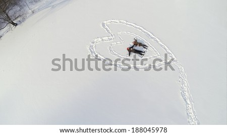 Aerial view to couple holding hands while lying on the snow inside the heart - stock photo