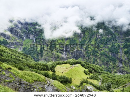 Aerial view to green meadow with house among mountains and waterfalls - stock photo