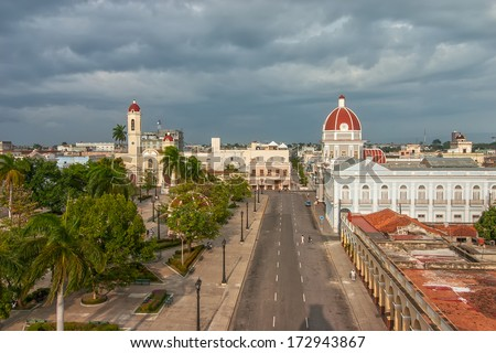 Aerial view to Jose Marti park with Town Hall and Cathedral of the Immaculate Conception lit by evening sun under heavy clouds shown on 5 May 2008 in Cienfuegos, Cuba