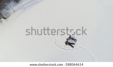 Aerial view to man and girl holding hands while lying on the snow inside the heart - stock photo