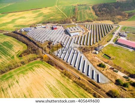Aerial view to solar power plant in agricultural landscape. Industrial background on renewable resources theme. - stock photo