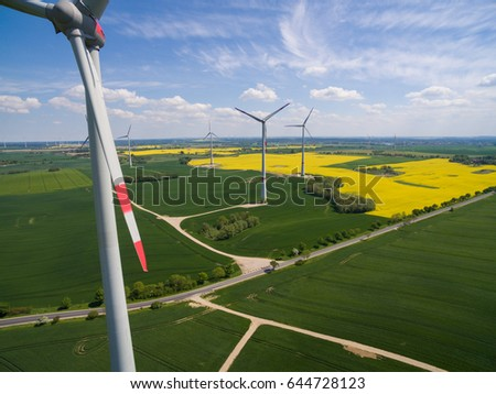 aerial view - wind turbines in beautiful  agricultural fields under blue sky - wind turbines power and green energy
