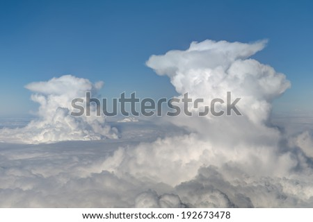 aerial viewof  two cumulonimbus clouds on blue sky background - stock photo