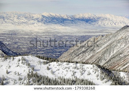 Aerial zoomed view from the top of Snowbird Ski Resort, in Utah looking down over Salt Lake City in winter. - stock photo