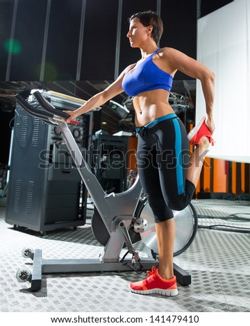 Aerobic woman stretching exercises after workout at gym - stock photo