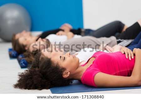 Aerobics class practicing deep breathing for relaxation lying on their backs on their mats on the floor with focus to a young African American woman in the foreground