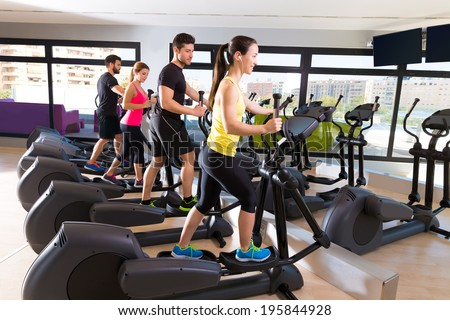 Aerobics elliptical walker trainer group at fitness gym workout - stock photo