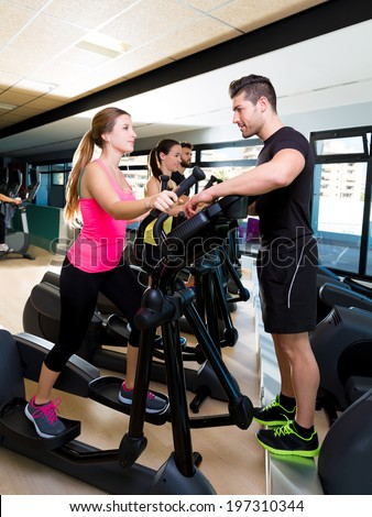 Aerobics elliptical walker trainer personal trainer man at fitness gym workout - stock photo
