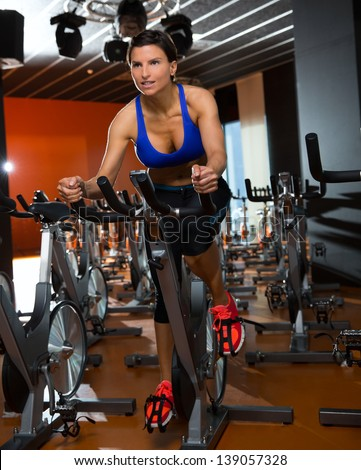 Aerobics spinning woman exercise workout at bikes gym - stock photo