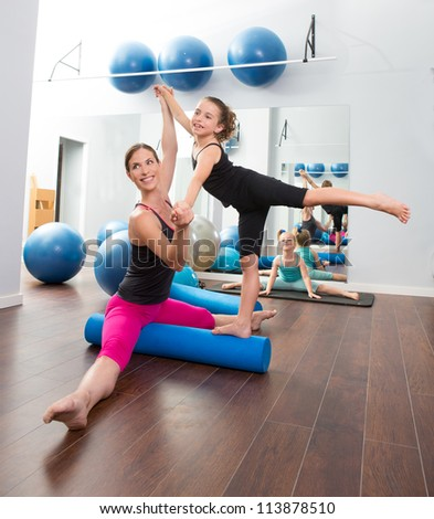 Aerobics woman personal trainer of children girl stability with foam roller - stock photo