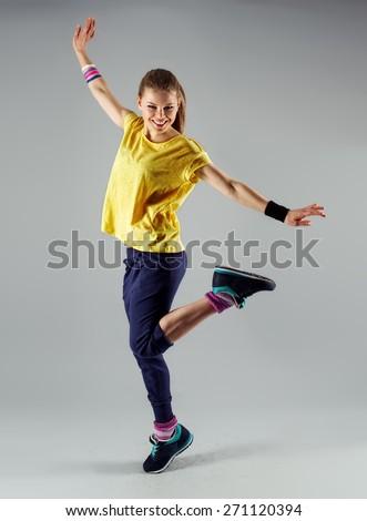 Aerobics woman. Portrait of pretty smiling girl training street dance on studio background. - stock photo