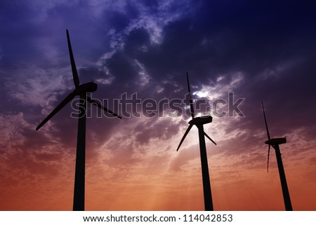aerogenerator windmills on dramatic sunset sky green electric energy